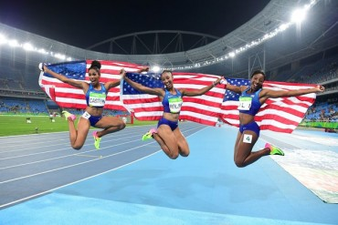 (L-R) Bronze medallist USA's Kristi Castlin, gold medallist USA's Brianna Rollins and silver medallist USA's Nia Ali celebrate after the Women's 100m Hurdles Final during the athletics event at the Rio 2016 Olympic Games at the Olympic Stadium in Rio de Janeiro on August 17, 2016.   / AFP / FRANCK FIFE        (Photo credit should read FRANCK FIFE/AFP/Getty Images)